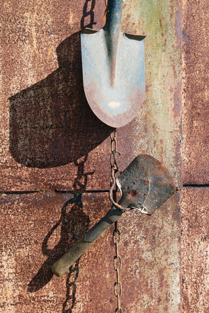 On the rusty metal wall of the village shed  hang on the chains used  old vintage agricultural tools. Sunny spring day shot