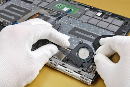 Computer notebook  repair -   technician disconnects the cooling fan.  Industrial closeup concept  shot