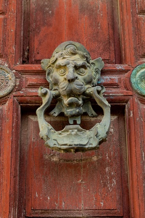 Detail of an ornate door knocker on the door of a building photo
