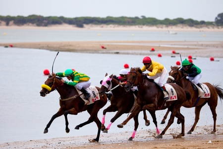 SANLUCAR DE BARRAMEDA, CADIZ, SPAIN - AUGUST 07: Unknown riders of the horses races of the beach of Sanlucar de Barrameda on August 07, 2010 in Sanlucar de Barrameda, Cadiz, Spain.