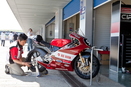 superbike: JEREZ DE LA FRONTERA, SPAIN - APR 17: 125cc Motorcycle of Mori Syunya in the pitlane being reparing by a mechanic in the CEV Championship on April 17, 2011, in Jerez de la Frontera, Spain. Editorial