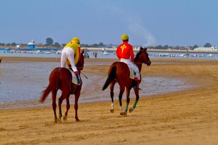 SANLUCAR DE BARRAMEDA, CADIZ, SPAIN - AUGUST 11: Unidentified riders at the start of race horses on Sanlucar de Barrameda beach on August 11, 2011 in Sanlucar de Barrameda, Cadiz, Spain.