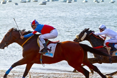 SANLUCAR DE BARRAMEDA, CADIZ, SPAIN - AUGUST 10: Unidentified riders race horses on Sanlucar de Barrameda beach on August 10, 2011 in Sanlucar de Barrameda, Cadiz, Spain.
