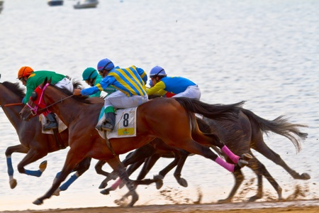 SANLUCAR DE BARRAMEDA, CADIZ, SPAIN - AUGUST 11: Unidentified riders race horses on Sanlucar de Barrameda beach on August 11, 2011 in Sanlucar de Barrameda, Cadiz, Spain.
