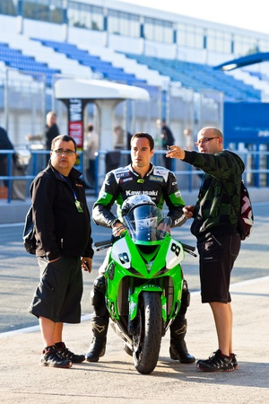 JEREZ DE LA FRONTERA, SPAIN - APR 16: Kawasaki Ninja Cup motorcyclist Adria Araujo speaks with the engineers in the CEV Championship race on April 16, 2011 in Jerez de la Frontera, Spain.