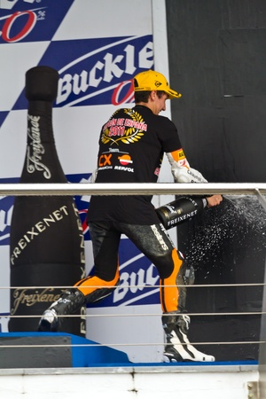 JEREZ DE LA FRONTERA, SPAIN-NOV 20: 125cc motorcyclist Alex Rins on the podium like winner of the 125cc CEV Championship celebrating with champagne on November 20, 2011, in Jerez de la Frontera, Spain Stock Photo - 11521043