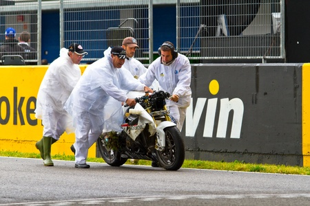 JEREZ DE LA FRONTERA, SPAIN - NOV 20: Race Stewards removing the motorcycle of Miguel Lopez from the track in the CEV Championship race on November 20, 2011 in Jerez de la Frontera, Spain