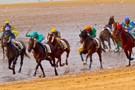 SANLUCAR DE BARRAMEDA, CADIZ, SPAIN - AUGUST 11: Unidentified riders of the accidented horses races of the beach of Sanlucar de Barrameda on August 11, 2011 in Sanlucar de Barrameda, Cadiz, Spain.