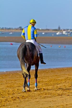 SANLUCAR DE BARRAMEDA, CADIZ, SPAIN - AUGUST 10: Unidentified rider at the start of race horses on Sanlucar de Barrameda beach on August 10, 2011 in Sanlucar de Barrameda, Cadiz, Spain. Stock Photo - 11817291