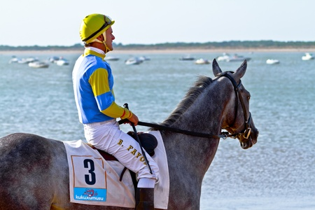SANLUCAR DE BARRAMEDA, CADIZ, SPAIN - AUGUST 10: Unidentified rider at the start of race horses on Sanlucar de Barrameda beach on August 10, 2011 in Sanlucar de Barrameda, Cadiz, Spain. Stock Photo - 11887754
