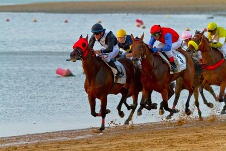 SANLUCAR DE BARRAMEDA, CADIZ, SPAIN - AUGUST 10: Unidentified riders race horses on Sanlucar de Barrameda beach on August 10, 2011 in Sanlucar de Barrameda, Cadiz, Spain. Stock Photo - 11887824