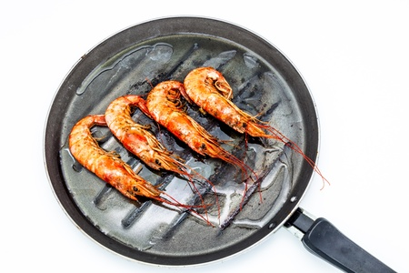 Grilled shrimp on a griddle on a white background photo
