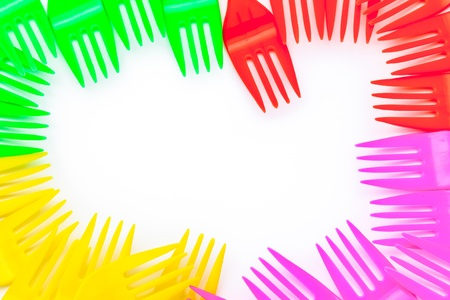 Multi colored plastic cutlery on a white background
