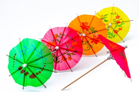 Several cocktail umbrellas on a white background photo