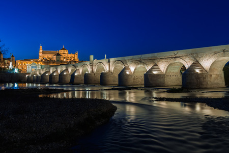 Cityscape of Cordoba at sunset with roman bridge and Mezquita, Andalusia, Spain photo