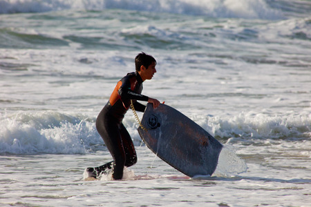bodyboarding: SAN FERNANDO, CADIZ, SPAIN - FEB 19: Unidentified bodyboader leaving the water on the 2nd championship of Surf and BodyBoard Impoxibol on Feb 19,2011 on the beach of San Fernando, Cadiz, Spain