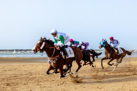SANLUCAR DE BARRAMEDA, CADIZ, ESPAÑA - 27 DE AGOSTO: Los jinetes no identificados compiten con la segunda raza de caballos llamada Fundacion Cajasol el 27 de agosto de 2016 en Sanlucar de Barrameda, Cádiz, España.