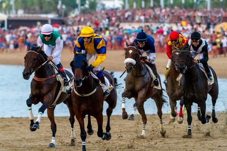 SANLUCAR DE BARRAMEDA, CADIZ, SPAIN - AUG 27: Unidentified riders race the fourth horses race called CKV Seguros on August 27, 2016 in Sanlucar de Barrameda, Cadiz, Spain. Editorial