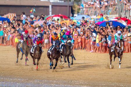 SANLUCAR DE BARRAMEDA, CADIZ, SPAIN - AUG 27: Unidentified riders race the second horses race called Fundacion Cajasol on August 27, 2016 in Sanlucar de Barrameda, Cadiz, Spain. Editorial