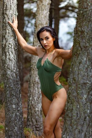 Fitness girl posing in the beach forest between  trees  with a beautiful green swimsuit