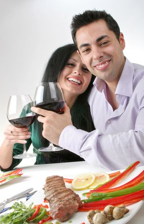 Couple having a romantic dinner with red wine, smiling looking at camera