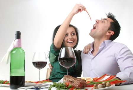 Couple having a romantic dinner with a grilled steak and a bottle of red wine. Female holding a piece of red pepper