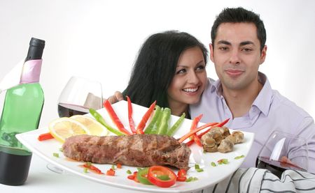 Couple having a romantic dinner with red wine, smiling, looking at camera