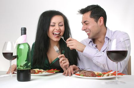 Couple having a romantic dinner with a grilled steak and a bottle of red wine. Male is feeding the woman