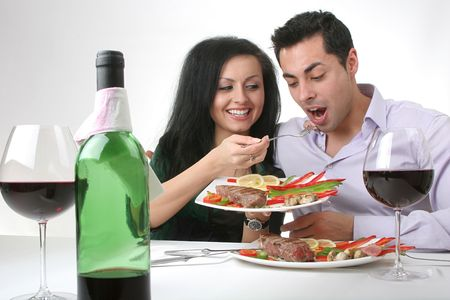 Couple having a romantic dinner with a grilled steak and a bottle of red wine. Female is feeding the male.
