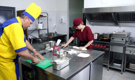 couple of cooks in action in a restaurant kitchen photo