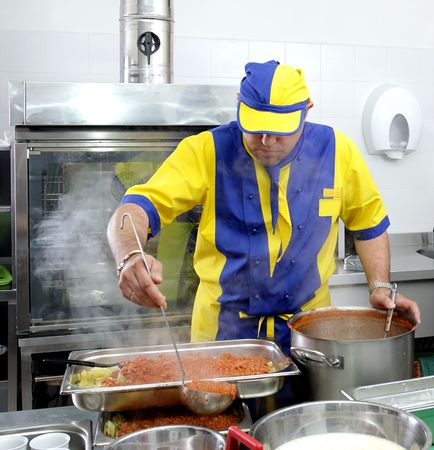 A cook is stirring a hot dish