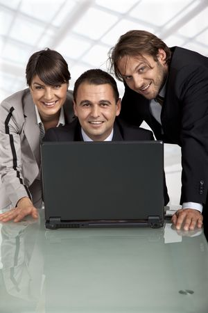 three happy business people behind a laptop, looking at camera