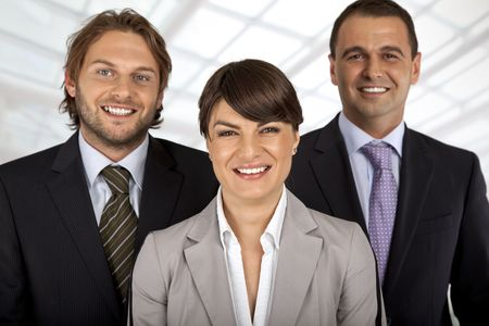 business team of three, female in front, two males behind, all smiling
