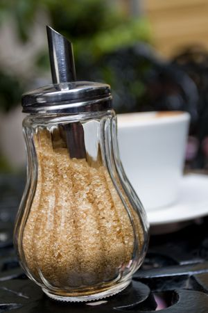 sugar-bowl on a cafe table, full of brown sugar with a cup of coffee behind
