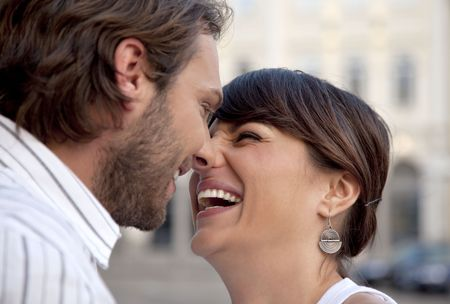 beautiful female and attractive male kissing and laughing