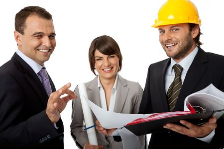 happy three people wearing suits, one with helmet holding plans, isolated on white