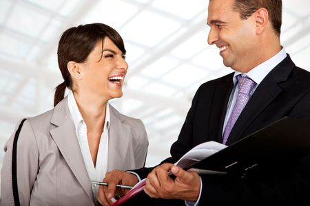 two business people wearing suits are laughing over files