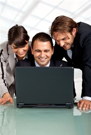 three happy businesspeople with a laptop, laughing Stock Photo - 5490003