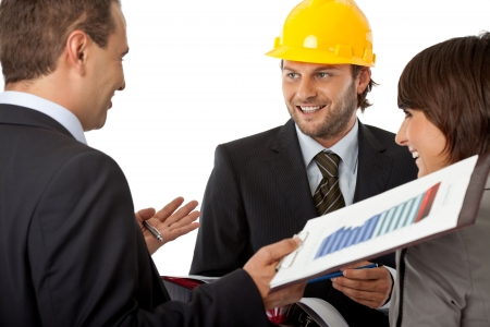 group of three wearing suits, one with a helmet, all smiling Stock Photo