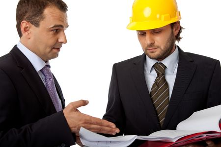 two business people, one with helmet are looking at plans Stock Photo