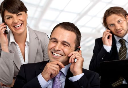 three happy business people talking on their cellular phones