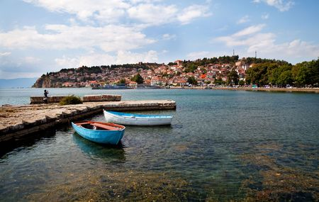 two boats by a quay, old town of Ohrid at the backgroud Stock Photo