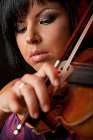 close-up of a young beautiful woman playing on a violin