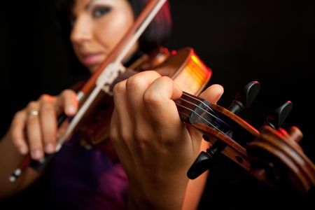 young beautiful female violinist, focus on her fingers