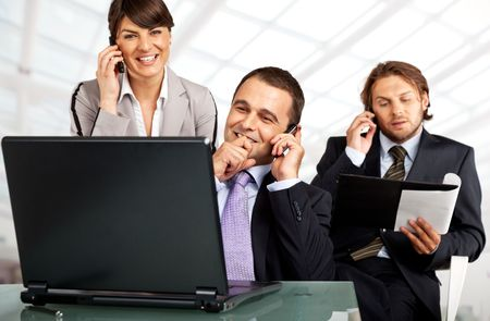 business team of three on their phones with a laptop