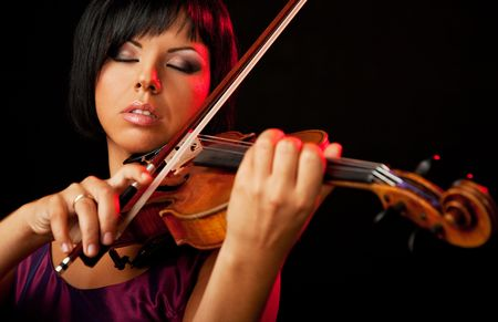 beautiful woman is playing a violin on black backround Stock Photo