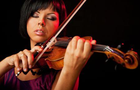 beautiful woman is playing a violin on black backround Standard-Bild