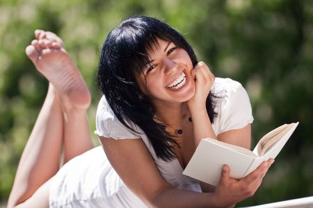 young female with white dress in the park with a book, laughing