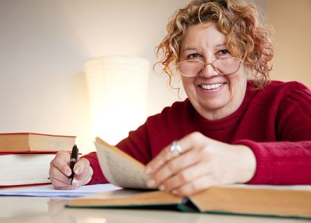 mature female is sitting by a table with books and a pen, smiling Stock Photo