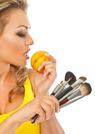 gorgeous female holding a peach in one hand and makeup brushes in other